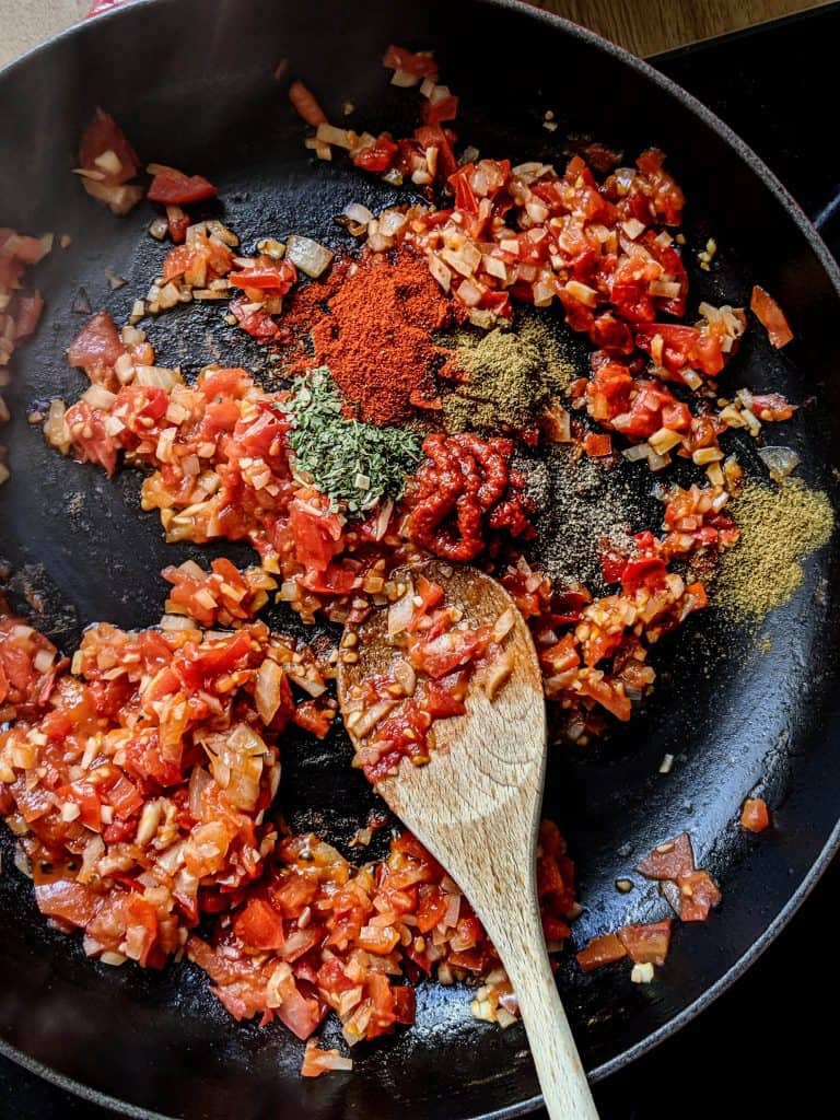 shakshuka in a cast iron pan with spices and tomato paste