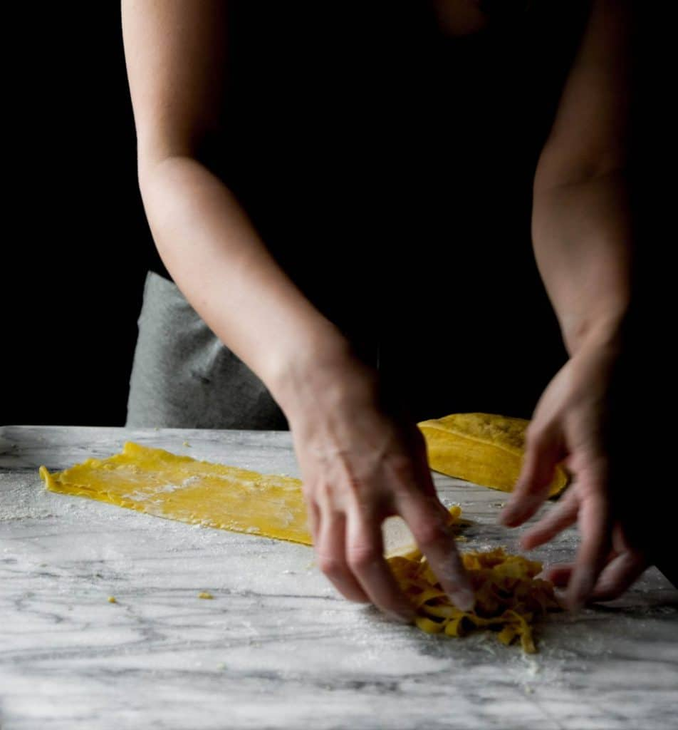 Rolling out and cutting fresh fettuccini pasta.