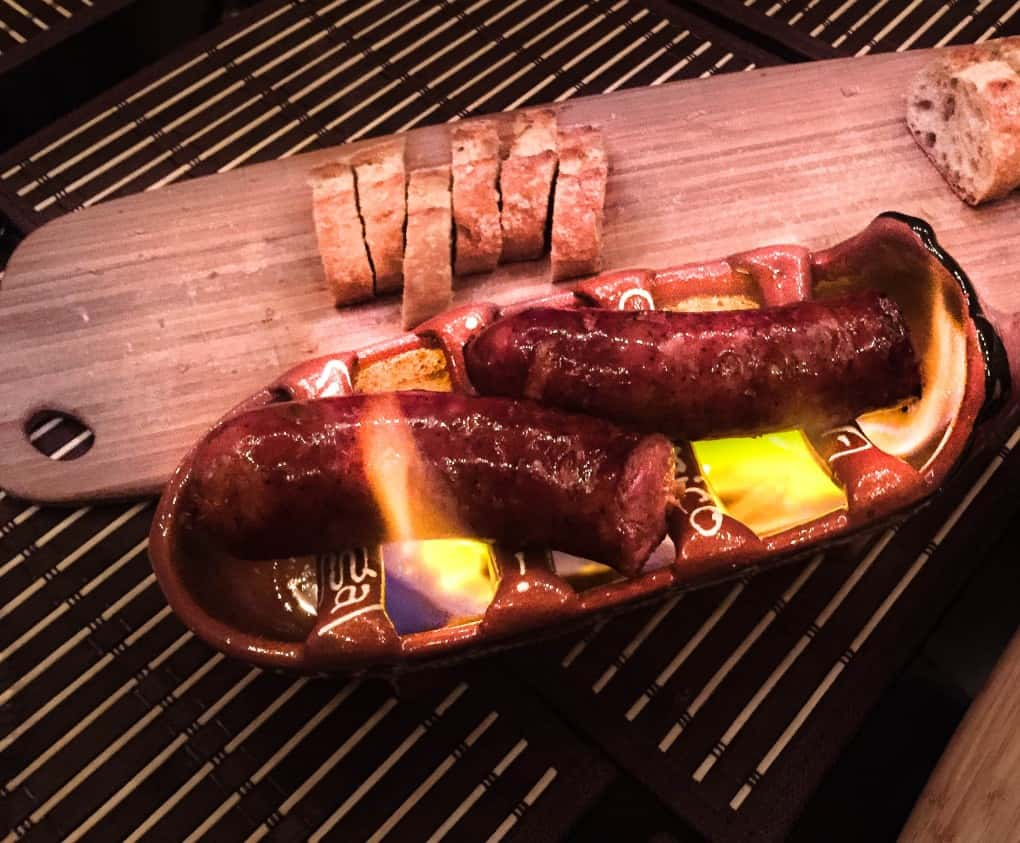 chorizo cooked Portuguese style over an open flame in a ceramic pig